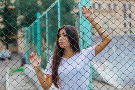 Portrait of a young brunette swag girl behind the rabitz fence. Stock Photo