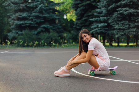 Portrait of a smiling charming brunette female sitting on her skateboard on a basketball court. Happy woman with trendy look taking break during sunset.