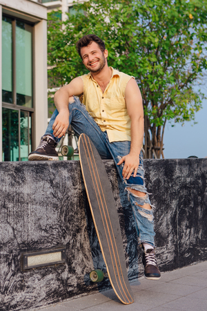 Young handsome man with beard sitting with longboard on the street. Stock Photo