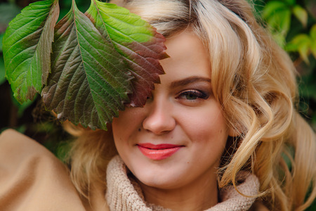Young beautiful woman in sweater and coat stands next to the background of wild grapes holding leaves close to the face in autumn park