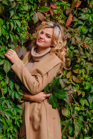 Young beautiful woman in sweater and coat stands next to the background of wild grapes holding bouquet of autumn leaves in park