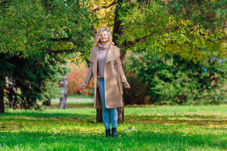 Beautiful elegant blonde woman dressed in a coat standing under the tree in autumn park. Sunny october day.
