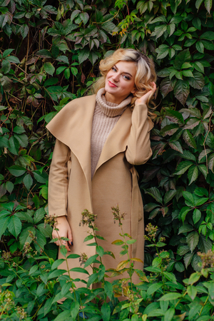 Young beautiful woman in sweater and coat stands next to the background of wild grapes leaves in autumn park