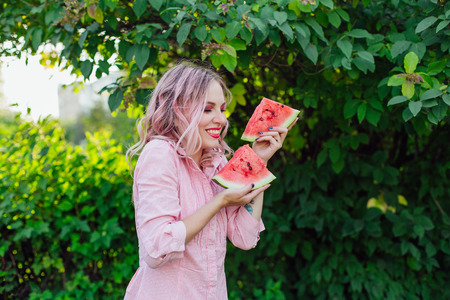 Beautiful young woman with pink hair holding two slices of sweet juicy watermelon Stock Photo