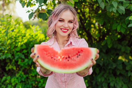 Beautiful smiling young woman with pink hair holding sweet juicy watermelon in hands