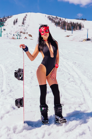 Attractive young woman dressed in swimsuit and mask with snowboard on the slope