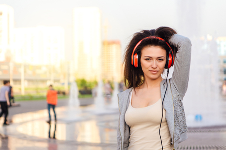 Young beautiful brunette woman listening to music streaming with headphones and dancing on the street.