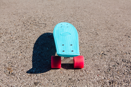Blue plastic skateboard penny board with pink wheels stands on the track.