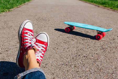 Close up of feet of a girl in red sneakers and blue plastic penny skate board with pink wheels on the background. Urban scene, city life. Sport, fitness lifestyle. Stock Photo