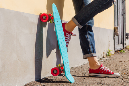 Close up feet of a girl in red sneakers and blue penny skate board with pink wheels standing next to the wall. Urban scene, city life. Sport, fitness lifestyle.
