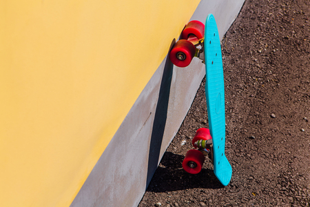Blue plastic skateboard penny board with pink wheels stands next to the wall.