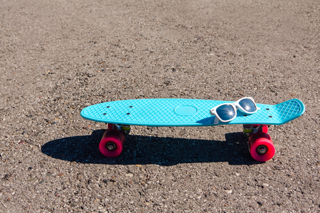 Sunglasses on a blue plastic skateboard penny board with pink wheels stands on the track. Stock Photo