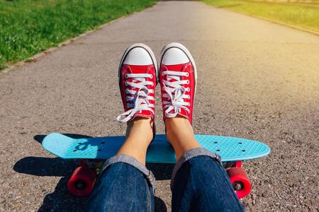 Close up van de voeten van een meisje in rode sneakers rijdt op blauwe plastic penny skate board met roze wielen. Stedelijk tafereel, stadsleven. Sport, fitness levensstijl.