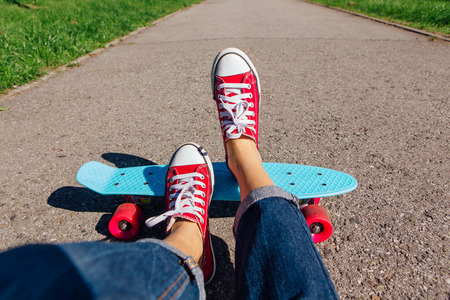 Close up of feet of a girl in red sneakers rides on blue plastic penny skate board with pink wheels. Urban scene, city life. Sport, fitness lifestyle.