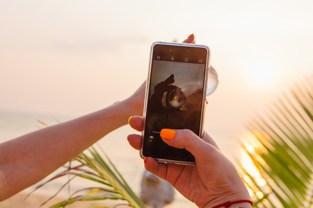 Woman shooting crystal lens ball with smartphone with reflection of sea and sunset on the beach Archivio Fotografico