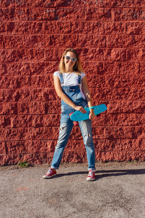 Portrait of a smiling woman dressed in overalls and sunglasses standing with her skateboard next to the red wall. Banco de Imagens