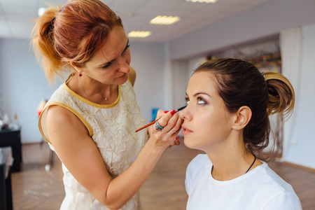 Make-up artist working in studio with young beautiful woman.