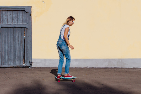 Portrait of a smiling woman dressed in overalls and sunglasses riding on her plastic skateboard next to the old wooden wall. Stock Photo