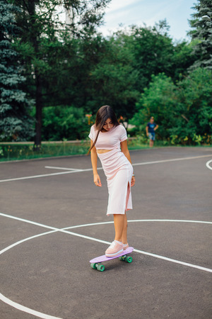 Portrait of a smiling charming brunette female standing on her skateboard on a basketball court. Happy woman with trendy look taking break during sunset.