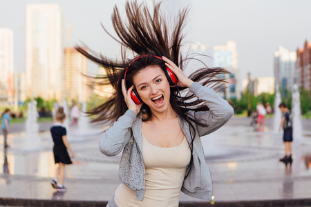 Girl listening to music streaming with headphones and dancing on the street. Stock Photo