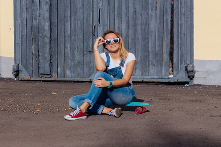 Portrait of a smiling woman dressed in overalls and sunglasses sitting on her skateboard next to the old wooden wall. Stock Photo