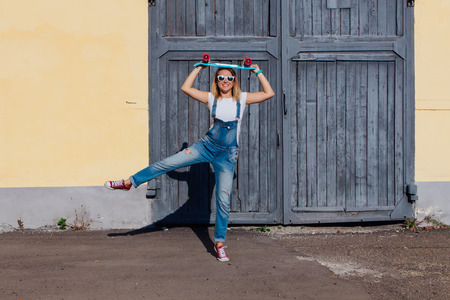 Portrait of a smiling woman dressed in overalls and sunglasses standing with her skateboard next to the old wooden wall.