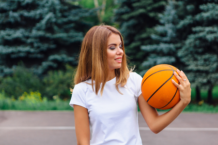 Beautiful young blonde girl dressed in white t-shirt, plays with ball on a basketball court outdoors. Copy space.