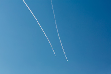 Two planes with traces on a blue sky background. Copy space