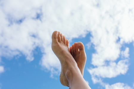 Female feet up infront of the blue cloudy sky