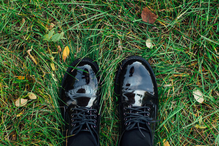 Two feet in black lackered shoes stepping on the green grass with fallen autumn leaves. Stock Photo