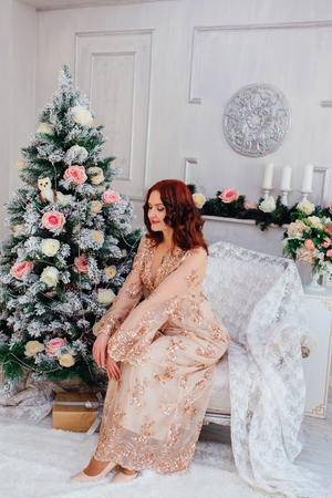 Beautiful young red hair woman in elegant pink dress sitting next to white christmas tree. Christmas glamour photo