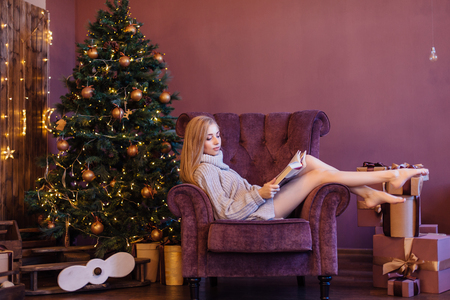 Beautiful young woman dressed in a sweater sitting on the cozy arm chair next to the christmas tree with gifts and reading book. Christmas cozy photo