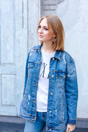 Fashion girl standing near brick wall in denim oversized jacket and beautiful ear rings.