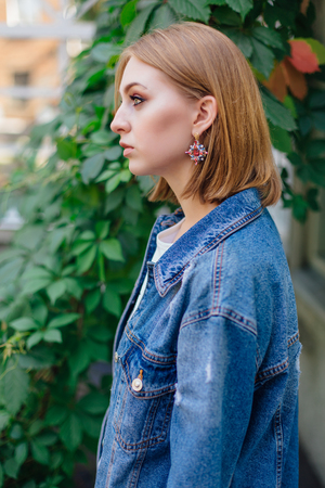 Fashion girl standing outdoors in denim oversized jacket and beautiful ear rings.