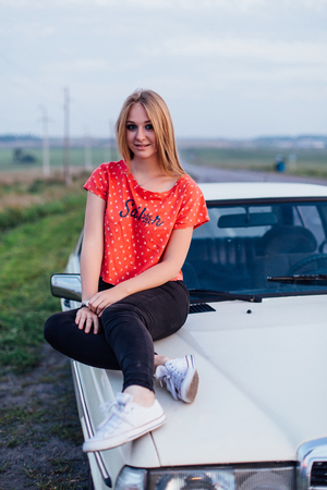 Portrait of a beautiful young woman sitting on the old car in retro style with bright makeup at sunset Stock Photo