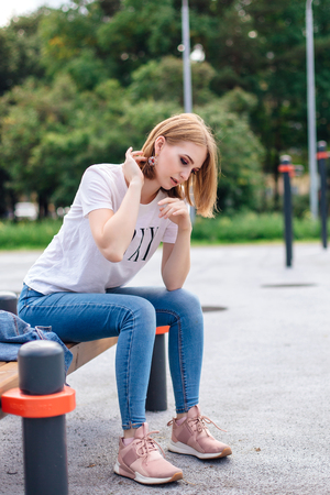 Fashion girl sitting on the bench in park, dressed in white t-shirt, jeans and beautiful ear rings.