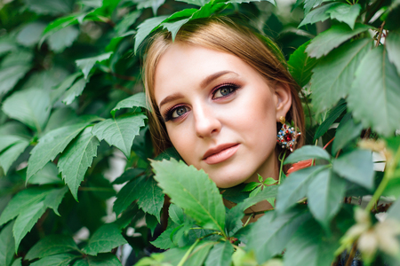 Portrait of a young beautiful woman with make up and ear rings, hiding in leaves of grapes.