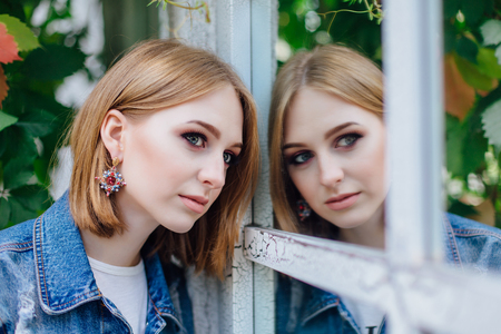 Fashion girl standing near mirror window in denim oversized jacket and beautiful ear rings, waching at her reflection.