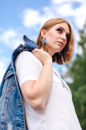 Fashion girl standing outdoors with denim oversized jacket and beautiful ear rings.