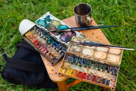 Palette of watercolor paints and brushes on the wooden background, close up.