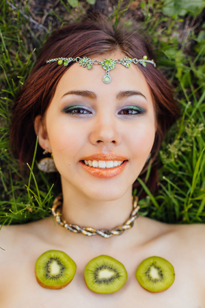 Beautiful young asian woman dressed in green dress laying on the grass with slices of kiwi on the chest