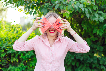 Beautiful young woman with pink hair holding two slices of sweet juicy watermelon in front of her face
