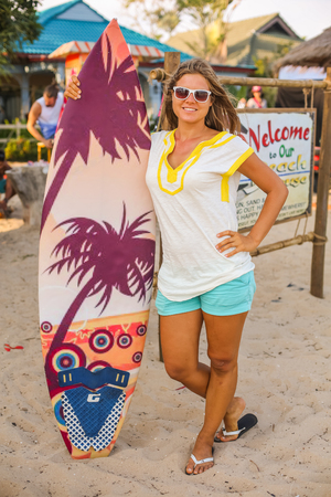 Smiling girl with a big surf board stands on the beach.