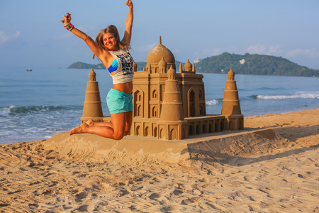 Young happy woman jumping high on the sandy beach next toTaj Mahal made of sand