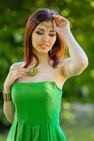 Beautiful young asian woman dressed in green dress with slice of kiwi on the chest