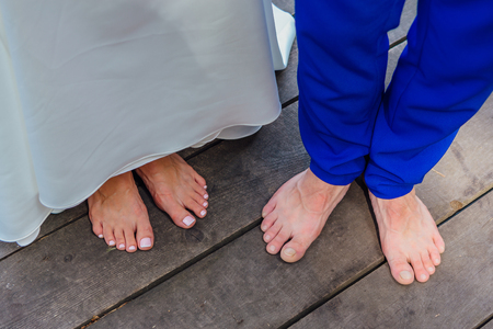 Front view of wedding couple's feet standing on the wooden bridge.