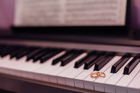 Two golden wedding rings laying on the piano keys