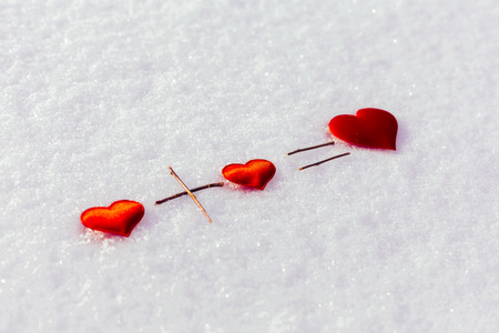 Mathematical equation with hearts the snow. Two small red hearts and one big. Love. Background Valentine's Day.Valentine's day cards. 免版税图像