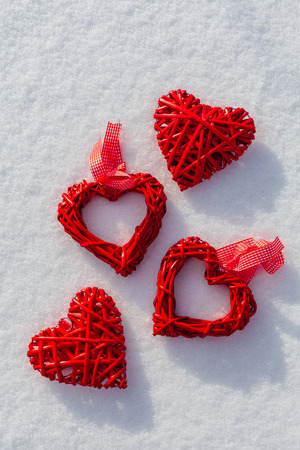 Red hearts on glittering snow. Vilentine's day theme. Love symbol.