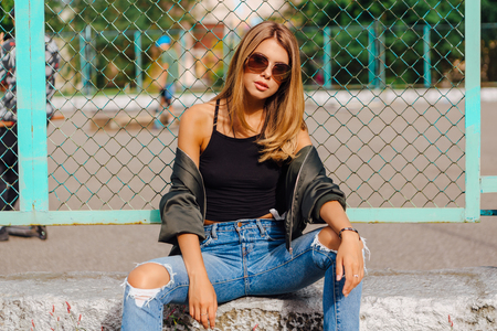 Fashion portrait of trendy young woman wearing sunglasses, and bomber jacket sitting next to rabitz in the city. Copy space.
